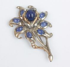 Very nice older brooch with blue cabochons set in silver tone pot metal accented by clear rhinestones. 3 1/2 inches long. Very good vintage condition.  To see more photos or purchase https://www.etsy.com/listing/49857244...