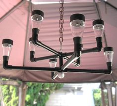 Contemporary style solar outdoor chandelier. Materials - PVC pipe and fittings, white solar lights, wooden knob. Chain and carabiner clip not