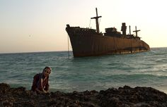 A woman poses for a picture in front of the beached Greek ship Moula F, during sunset off Kish Island