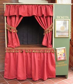 Old entertainment center turned into a puppet theatre with a tension rod for the curtains, velcro dots to tie back the curtains and I love how she made the black background to keep the puppeteers out of site.