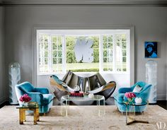 In the living room of a Connecticut home designed by Joe Nahem, walls painted in Benjamin Moore's San Antonio Gray offset an Andy Warhol silkscreen and a pair of 1960s Carlo Nason floor lamps. A Ron Arad sofa and a Karl Springer Lucite cocktail table from Lobel Modern are flanked by '30s Gio Ponti armchairs; the 19th-century rug is from Beauvais Carpets. The sculpture on the lawn is by Peter Coffin.