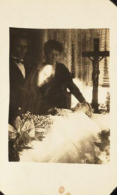 Mourning. ~ Quite strange: a third face all white and surrounded by a black mantilla or scarf seems to look right into the camera (in the middle of the two standing people, left side under the woman´s head). Not sure what it really is. I am grateful for your advice.