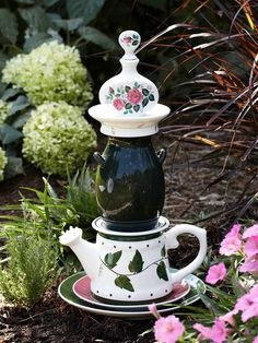 Plates, a teapot, a vase, a fancy dish, and a floral perfume bottle stack up to create a garden fancy about 20 inches tall. A hydrangea, red fountaingrass, and pink petunia appear to be paying homage to this nifty design.