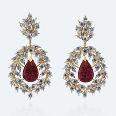 A wreath of tiny leaves in white gold and sapphires, with a yellow gold branch, holds a drop-shaped ruby engraved with a floral motif. Combining gold of different colors enhances the intensity of the red gems, making them the real stars of these delicate, beautiful earrings Http://www.facebook.com/diamonddreamfinejewelers http://www.twitter.com/diamond_dream_ http://www.instagram.com/diamonddreamjewelers