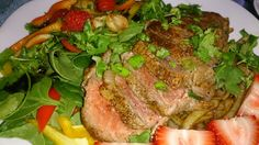Dry rubbed steak on top of grilled onions with spinach, red and yellow bell peppers salad dressed with blackcurrent balsamic vinager... Yummy :)