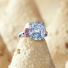A cushion-shaped fancy vivid blue diamond weighing carats, flanked on each side by an oval pink diamond weighing and carat respectively, mounted in platinum. Colored Diamond Rings, Pink Diamond Ring, Colored Diamonds, Diamond Jewelry, Diamond Trade, Blue Diamonds, Green Diamond, Blue Rings, Pink Sapphire