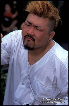 Japanese man with dyed hair and fierce gesture, Asakusa festival, Tokyo, Japan by Frantisek Staud