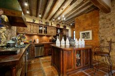 Gourmet kitchen with beamed ceiling, fireplace, restaurant stove and wine storage. #agavesanmiguel #sanmiguelrealestate