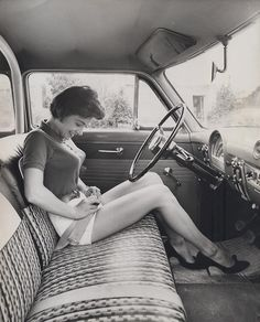 Cars used to have a bench front seat. Meanwhile- her outfit is fabulous!