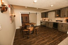 Wet Bar in Finished Basement  #wet #bar #finished #basement #rustic #hardwood #flooring #lighting #barn #door #wine #cellar #backsplash #sink #fridge #microwave #dishwasher #cabinets #granite #countertops #3 #pillar #homes #model #home #builder #custom #plain #city #ohio #dublin #schools #luxury #dream #real #estate