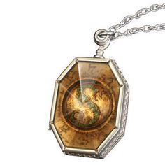 """Add this Horcrux locket to your Harry Potter collection.  This locket is an authentic prop replica of the real Horcrux locked seen in the <I>Harry Potter and the Deathly Hallows - Part 1<I> film.  Locket features a green crystal """"S"""" and measures approximately 2 inches, with a 24-inch chain.  Collector display box included."""