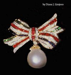 Imelda Marcos; Large pearl pendant surrounded by diamonds, rubies, sapphires and emeralds in a bow, inset into yellow gold.