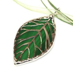 This is a Stained Glass Filigree Pendant in a Leaf Design. A composition of green tones were selected to give the leave a natural appearance.