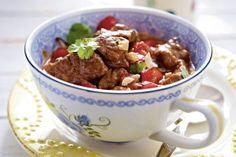 Rinder-Kokos-Curry Rezept: Rindfleisch,Knoblauchzehen,Ingwer,Paprikaschoten,Öl,Pfeffer,Kokosmilch,Sojasoße,Lauchzwiebeln,Koriander,Erdnüsse