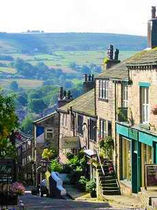 Haworth Main Street. Haworth is a village in the City of Bradford metropolitan borough of West Yorkshire, England. It is located in the Pennines, 3 miles southwest of Keighley and 10 miles west of Bradford. The surrounding areas include Oakworth and Oxenhope. Wikipedia