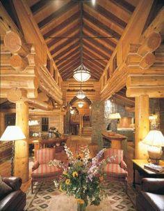 Elegant Log Home Interiors   Quietly elegant armchairs and leather sofas civilize the massive logs ...