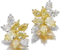 Pair of fancy intense and fancy yellow diamond and diamond ear clips.     Each of cluster design set with pear-shaped fancy intense yellow, fancy yellow and near colourless diamonds weighing from 0.72 to 2.02 carats, post fittings.    Sotheby's.