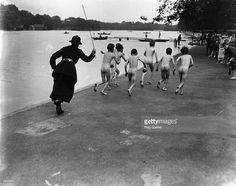 A British policewoman chasing after a group of naked street boys by the Serpentine in Hyde Park, London.