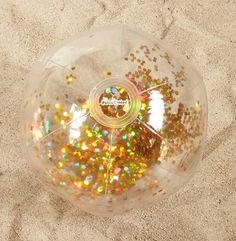 A clear beach ball by Pool Candy featuring iridescent gold confetti enclosed in the ball. - Beach Ball - Ideas of Beach Ball