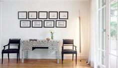 Com vista para o jardim, este hall conta com composição de quadros, cadeiras em tecido adamascado e escrivaninha marroquina