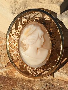 Hand carved shell cameo set in a lacy filigree setting with a heart design. Setting is a brooch. 1/20 12k gold filled and marked as such. Pin back has locking
