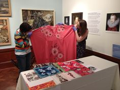 Museum staff show off a kimono from the Constance Howarth collection
