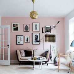 pink accent wall in the living room / gold mesh pendant light / sheepskin / gallery wall