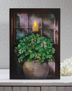 the candle flame in this Shamrock wall art lights up and flickers. Check out more designs from the Radiance Lighted Canvas collection ~ country designs, nautical designs, Christmas, Fall and Halloween and more Shelley B Home and Holiday
