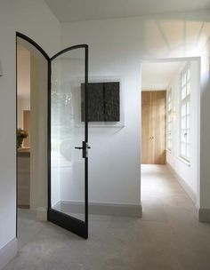 Fantastic interior glass door. I love the contrast of the black, curved frame with the square white ones.