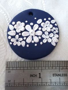 Polymer clay pendant, handmade with applique technique, one of a kind. Blue, with white flowers, leaves and dots. By Lis Shteindel.