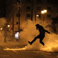 Greek youth kicks teargas canister back at police during riots over police shooting