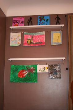 "Ikea hack: kids' art display shelf1 Ikea ""Ribba"" picture ledge, 45″ ($14.99) 1 Ikea ""Dignitet"" wire curtain rod ($12.99) 1 set Ikea ""Deka"" curtain wire clips ($6.99)"