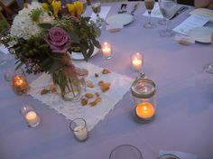 "Reception table centerpieces: flowers from Field of Flowers, Grandmas' mason jars, dried lavender and dried rose petals from Truly Living Well, and antique ""lady"" linen."