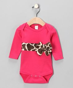 """Your darling is a little too young to pick out her clothes on her own, but you know if she could she would be crawling straight for this sweet silhouette. Rich pink and bold giraffe print covers her with a bit of little-lady chicness while the ribbon seals in some sweet. Dress her in an outfit that can't help but be """"awwed"""" at.100% polyesterHand wash; dry flatImported"""