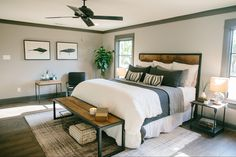 Masculine Bedroom - reclaimed wood and iron bench, side table, and headboard, wood floors, soft grey walls with dark grey trim, grey and white bedding, wire baskets for storage, fiddle leaf fig in the corner