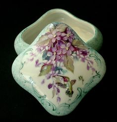 """This beautiful hand painted porcelain box which measures 3"""" long x 3"""" wide x 1-1/4"""" tall and is designed with fantasy flowers and a hungry broadtail hummingbird, bordered by Victorian scrolls. This piece is painted entirely by hand.  $26.96 + $5.95 shipping"""