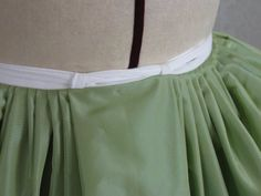 CoutureMayah.info - a great idea, attaching loops to the front of the petticoat, and threading the waist ties through, to keep the petticoat front from sagging.