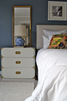 Our tan and navy master bedroom at www.rummageliving.com  #sidetable with mirror #campaign chest #gray campaign dresser # nailhead headboard # tall mirrors #navy wall #master bedroom #chiang mai pillow #ginger jar lamp #gold mirror