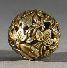 Lot 96: GOLD OJIME In ovoid form with openwork foliate design. Diameter 16mm. - Eldred's | Invaluable