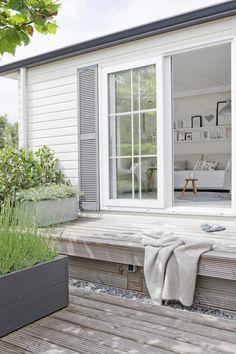 En gammel brakke er bygget om til et moderne og lekkert feriehus. Fra hytta går de rett ut på en platting som er stor nok til noen gode solstoler.