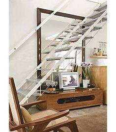 O móvel da TV (1,50 m x 54 cm, altura de 40 cm) aproveita o vão sob os degraus da escada de aço e alumínio e ainda recebe decoração especial, com flores e uma bandeja com taças.
