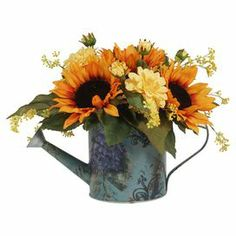 """Create a lush tablescape or charming vignette with this lovely faux sunflower arrangement, nestled in a delightful watering can.  Product: Faux floral arrangementConstruction Material: Silk, plastic and metalColor: Orange, yellow, green and blueFeatures:  Includes faux sunflowersHandmade   Dimensions: 12.5"""" H x 18"""" W x 18"""" DCleaning and Care: For Indoor Use Only"""