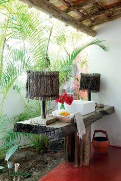 Bancada | A cuba fica sobre tábua rústica apoiada em tronco preparado por Elma Chaves. O banheiro social é aberto para o jardim interno (Foto: Evelyn Müller / Living Inside)
