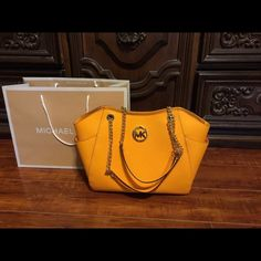 """MICHAEL  KORS JET SET TOTE BAG YELLOW Authentic Michael Kors New Style with Burnt Orange Saffiano Leather for the Upcoming Fall Season .Gold Tone Hardware; Two Side Slip Pockets; Top Zip Closure;Dual Leather Handles with Chain Detail ; Michael Kors Gold Logo ;Interior Pocket with Zip Closure . Four Interior Multi Function Slip Pockets Signature MK Lining 11"""" L x 9"""" H x 4"""" D 10""""Drop Care Card Included. MICHAEL Michael Kors Bags Shoulder Bags"""