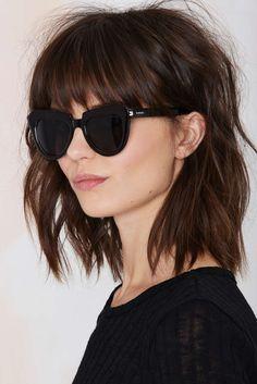 Chica usando un corte de cabello long bob en tonos chocolate con flequillo