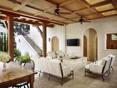Gorgeous covered patio with coffered ceiling featuring skylights and ceiling fans. The patio features stone exterior walls with arched doorways and stone tiled floors with a stone clad firepit. Black metal outdoor seating with white seat cushions surround the firepit area and wall mounted flat screen tv. To the left of the space stands a farmhouse style dining table lined with black Windsor chairs.