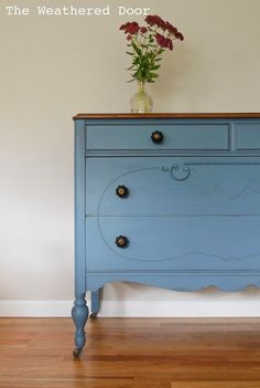 A smokey blue dresser with a stained top