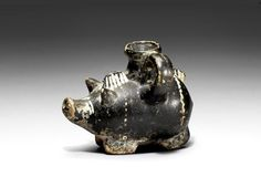 Gnathian baby feeder flask,  4th Century A.D. In the form of a pig, with details added in white and ochre, with short legs, curly tail and hirsute back, 7.5 cm high. Private collection
