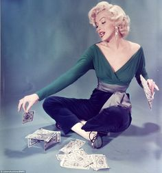 Marilyn posed coquettishly while building a tower out of dollar bills in an image shot by John Florea