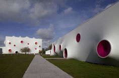 Olympic Shooting Venue by Magma Architecture. The façade is constructed out of a double curved membrane and the colourful dots act as tensioning nodes; the lower openings also serve to ventilate the space.